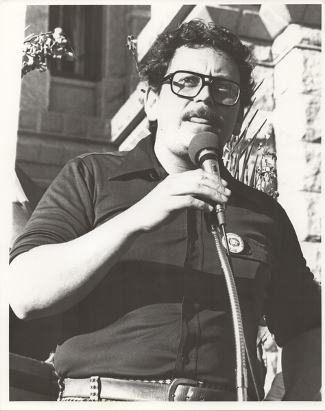 black and white photo of José Angel Gutiérrez speaking at a police brutality protest